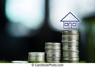 Double exposure of house on the top of stacks of coins on working table, finance and business concept,
