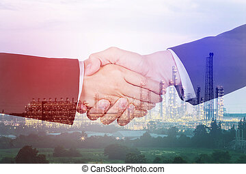 double exposure of shaking hand between businessman and businesswoman with oil refinery plant background