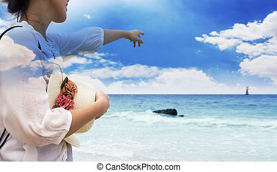 Double exposure of smiling young woman pointing finger blue sky on the beach