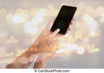 double exposure of woman hand holding the phone tablet and night city bokeh background