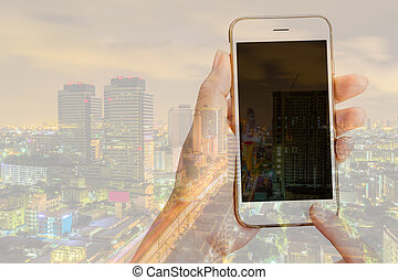 Double exposure of woman using her smart phone and city skyline night light background.