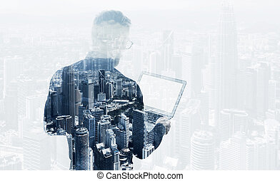 Double exposure young bearded businessman wearing black shirt holding contemporary notebook. Modern megalopolis background. Blank screen ready for your business message. Horizontal mockup