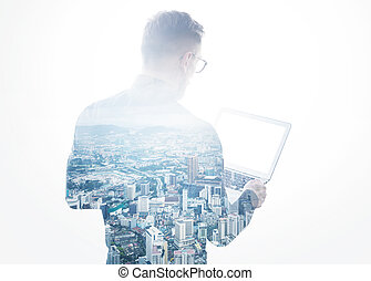 Double exposure young bearded businessman wearing black shirt holding contemporary notebook hands.Isolated white,modern city background.Blank screen ready for your business message.Horizontal mockup