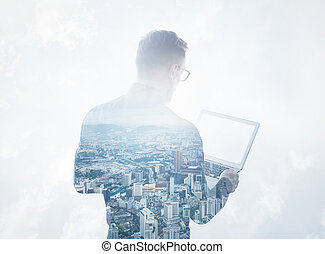 Double exposure young bearded businessman wearing black shirt holding contemporary notebook.Isolated white clouds,modern city background.Blank screen ready for your business message.Horizontal mockup