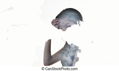 Double exposure. Young woman in evening dress against the background of clouds