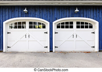 Double garage doors - Two white garage doors with windows on...