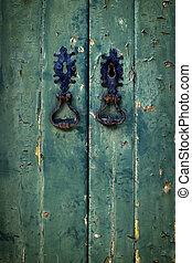 Double Green Door - Two black door handles in old green...