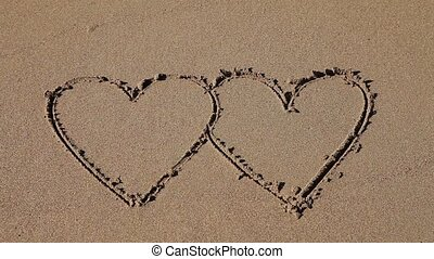 Double hearts drawn in the sand - Double hearts. A wave...