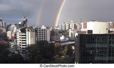 Double rainbow above city skyline.