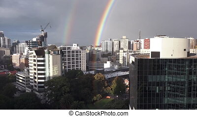 Double rainbow above city skyline.