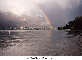 Double rainbow sky on Annecy lake and mountains, France