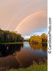 rainbow over autumn pond - double reflected rainbow over ...