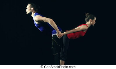 Double Standing Forward Bend - Close up of man and woman...