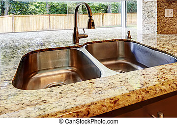 Double steel sink with and granite top. CLose up view