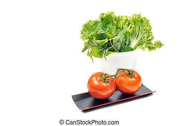 Double tomatoes lay on long black tray, Lettuce and Lemon balm in white bowl, clipping path included.
