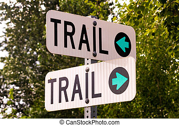 Double trail sign on a post with blue arrows