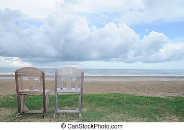 Double wooden chairs on beach