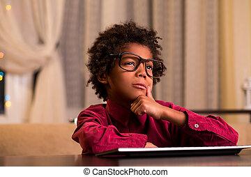 Doubtful black boy at keyboard. Unsure afro kid at keyboard....