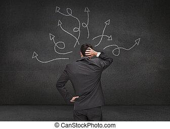 Doubtful businessman looking at arrows drawn on a grey wall