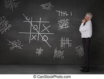 Doubtful businessman looking at tic-tac-toe drawn on the ...