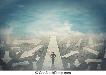 Doubtful person, hands on hips, choosing the way as multiple arrows on the road showing a mess of different directions. Choosing the correct pathway, difficult decision concept, confusion symbol.
