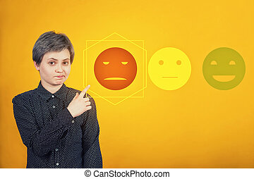 Doubtful woman hipster pointing index finger aside, uncertain face expression, choose negative feedback rating for bad customer service. Press on the sad face emoticon.
