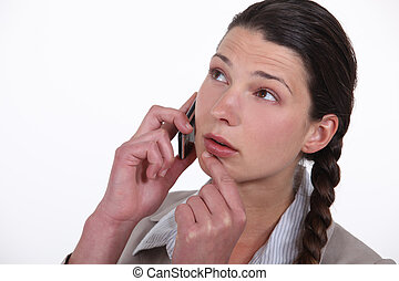 Doubtful woman talking on her mobile phone