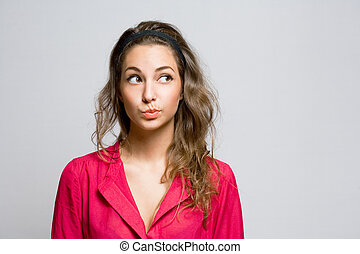 Doubtful young brunette woman.
