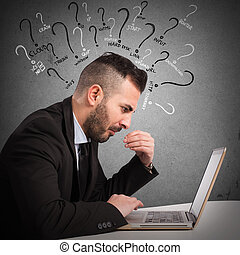 Doubts on computer use - Businessman with quizzical...