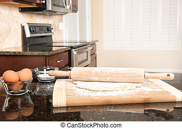 Dough and rolling pin in kitchen