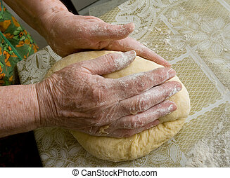 Hands of old woman making dough