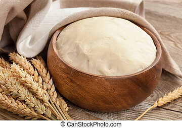 dough in a wooden bowl and ears of ripe wheat on the old boards. Rural concept.