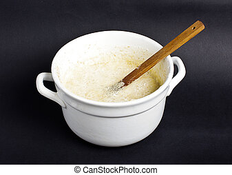 Mixing homemade bread dough in the white pot isolated on the black background