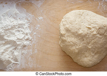Dough on a wooden desk background with dusting of flour