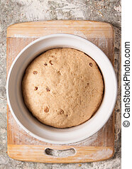 Dough rising in a bowl - A bread dough with sultanas or ...