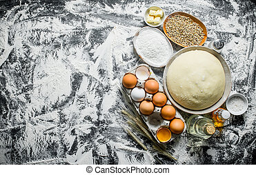 Dough with flour, grain and eggs. On rustic background