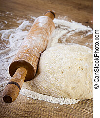 Dough with rolling pin on wooden table