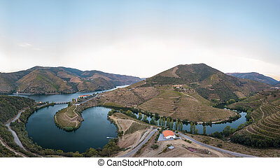 Douro valley wine region, Portugal. Vineyards landscape with beautiful farm. Tourist attraction and travel destination. Drone aerial top view. Bend shape river.