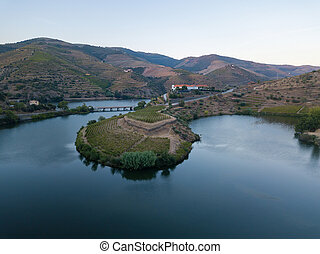 Douro wine valley region, Portugal. Vineyards landscape with beautiful farm. Tourist attraction and travel destination. Drone aerial top view. Bend shape river.