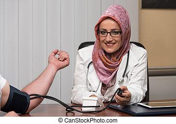 doutor, levando, muçulmano, jovem, homem, pressão, sangue