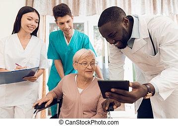 doutor, mostra, algo, ligado, a, tabuleta, para, um, idoso, paciente, em, um, amamentação, home.