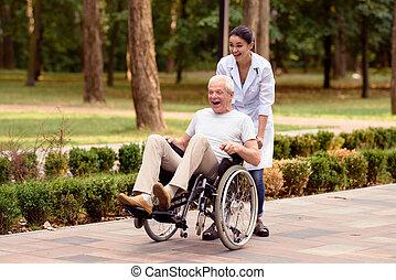 doutor, rolos, um, idoso, paciente, ligado, um, cadeira rodas, em, a, park., são, tendo divertimento