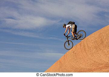 Down - A fearless mountain biker drops down a steep section...