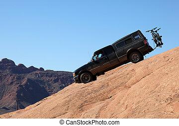 A four wheel drive pickup truck negociates a steep rock path near Moab