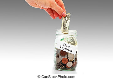 woman's hand putting money into a down payment coin jar - home buying concept