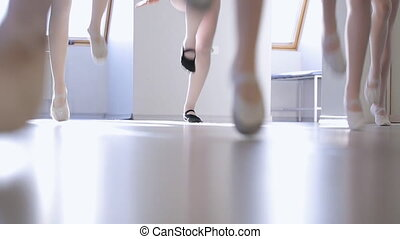 Down side view of young females feet jumping in model school.
