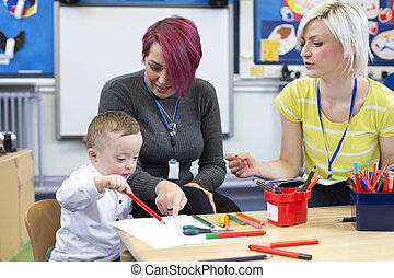 Down Syndrome boy at Nursery - Nursery teacher sitting with...