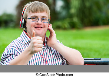 Down syndrome boy with headset doing thumbs up. - Close up...