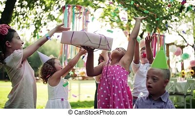 Down syndrome child with friends on birthday party outdoors ...