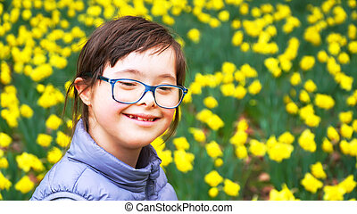 Down syndrome girl on background of flowers field